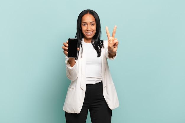 Jovem negra sorrindo e parecendo amigável, mostrando o número dois ou o segundo com a mão para a frente, em contagem regressiva. conceito de telefone inteligente
