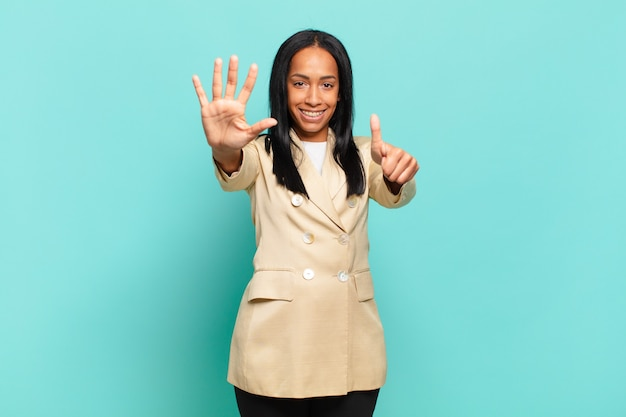 Jovem negra sorrindo e parecendo amigável, mostrando o número seis ou sexto com a mão para a frente, em contagem regressiva. conceito de negócios