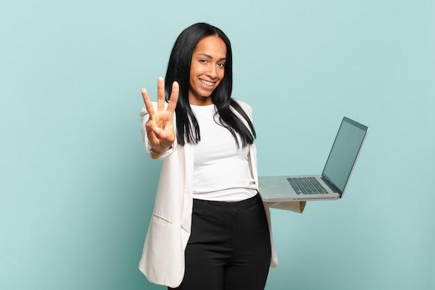 Jovem negra sorrindo e parecendo amigável, mostrando o número três ou terceiro com a mão para a frente, em contagem regressiva. conceito de laptop