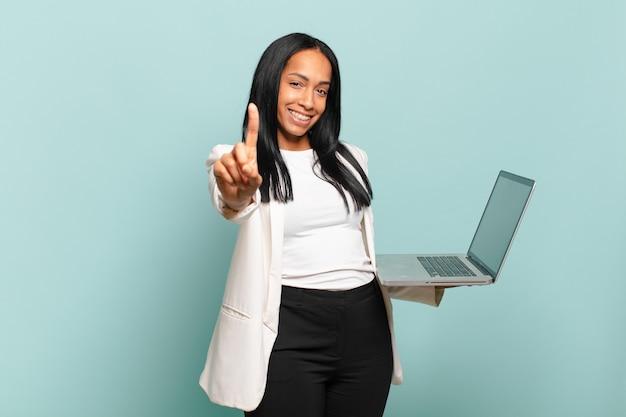Jovem negra sorrindo e parecendo amigável, mostrando o número um ou primeiro com a mão para a frente, em contagem regressiva. conceito de laptop
