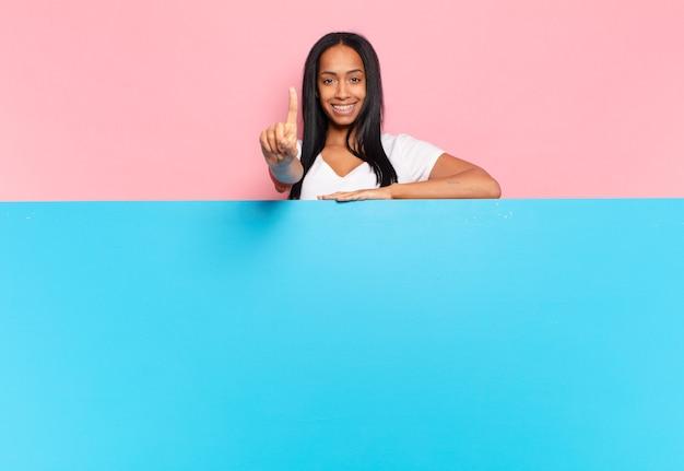 Jovem negra sorrindo e parecendo amigável, mostrando o número um ou primeiro com a mão para a frente, em contagem regressiva. copie o conceito de espaço