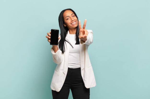 Jovem negra sorrindo e parecendo feliz, despreocupada e positiva, gesticulando vitória ou paz com uma mão. conceito de telefone inteligente