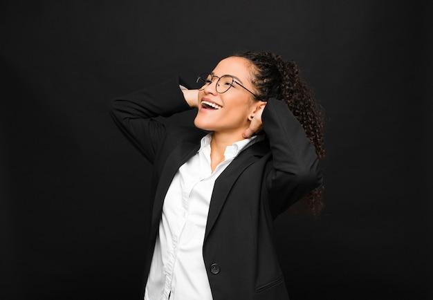 Jovem negra sorrindo e se sentindo relaxado, satisfeito e despreocupado, rindo positivamente e relaxando contra a parede preta