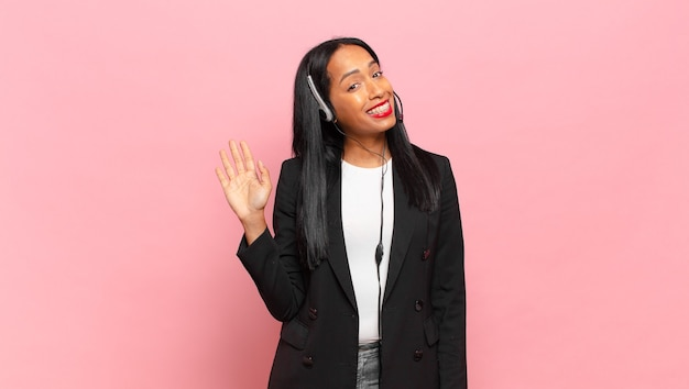 Jovem negra sorrindo feliz e alegre, acenando com a mão, dando as boas-vindas e cumprimentando ou dizendo adeus. conceito de telemarketing