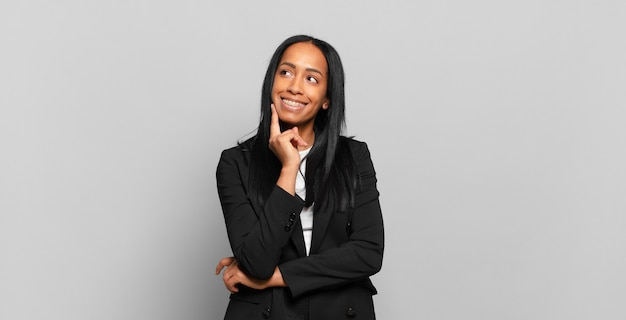 Jovem negra sorrindo feliz e sonhando acordada ou duvidando, olhando para o lado. conceito de negócios