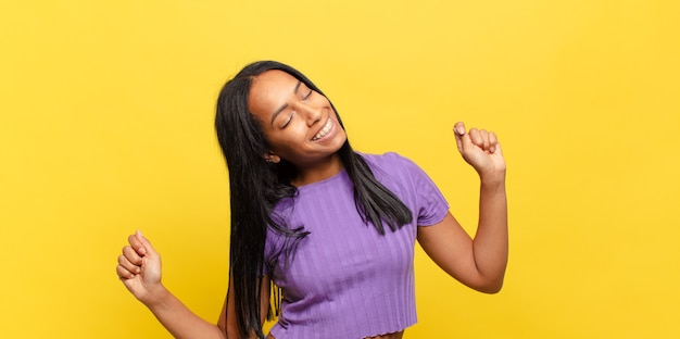 Jovem negra sorrindo, sentindo-se despreocupada, relaxada e feliz, dançando e ouvindo música, se divertindo em uma festa