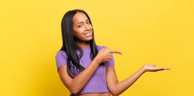 Jovem negra sorrindo, sentindo-se feliz, despreocupada e satisfeita, apontando para um conceito ou ideia no espaço da cópia ao lado