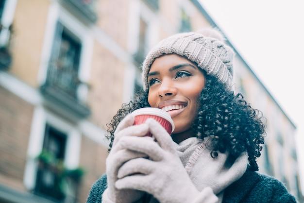Jovem negra tomando café vagando pelas ruas de madrid no inverno