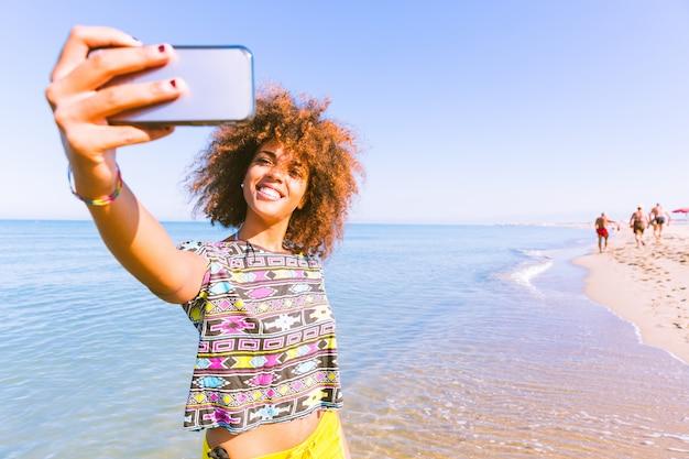 Jovem negra tomando uma selfie na praia