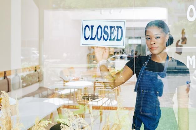 Jovem negra, triste proprietária de uma pequena empresa, precisa fechar seu café devido à crise econômica