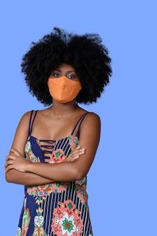 Jovem negra usando máscara facial isolada em fundo azul