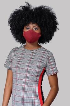 Jovem negra usando máscara facial isolada em fundo cinza