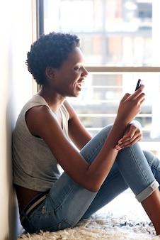Jovem negra usando telefone inteligente pela janela em casa