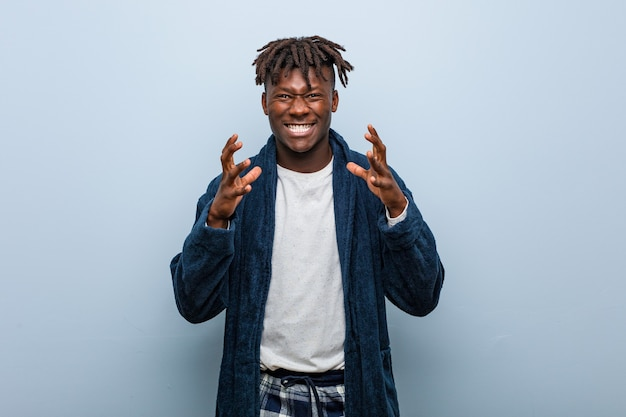 Jovem negro africano de pijama chateado, gritando com as mãos tensas.