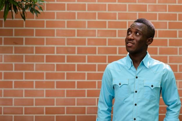 Jovem negro africano feliz sorrindo enquanto pensa