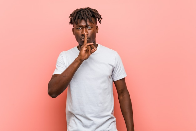 Jovem negro africano, mantendo um segredo ou pedindo silêncio.