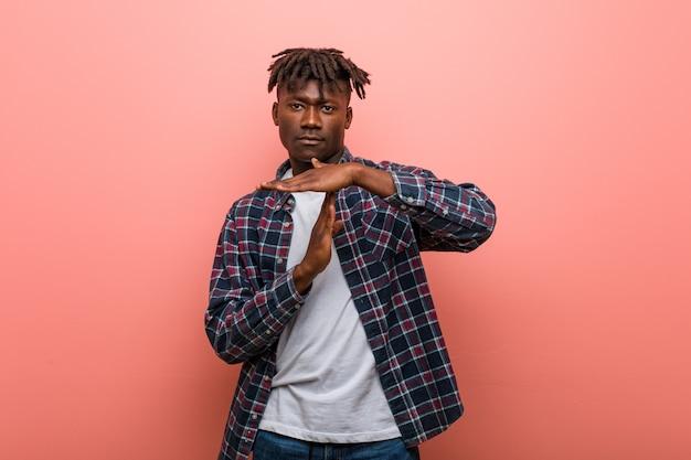 Jovem negro africano mostrando um gesto de tempo limite.