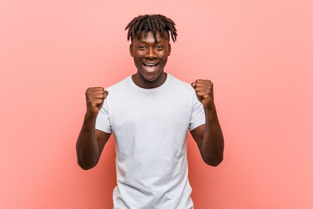 Jovem negro africano torcendo despreocupado e animado. conceito de vitória