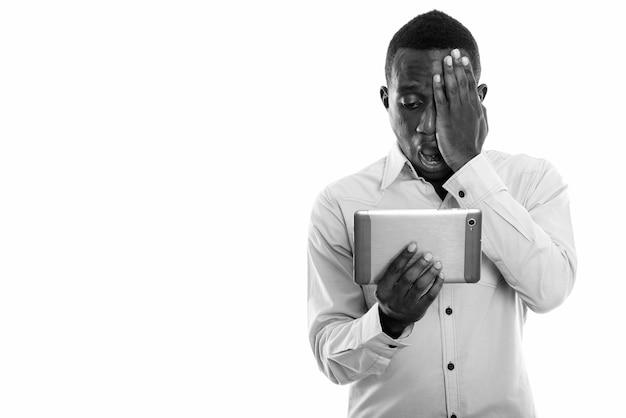 Jovem negro africano usando tablet digital enquanto cobre o rosto e parece chocado