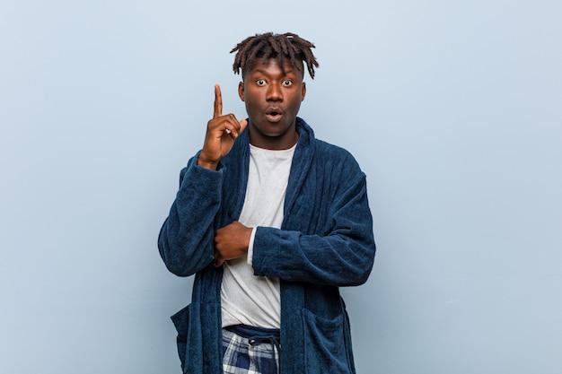 Jovem negro africano vestindo pijama, tendo uma ótima idéia, conceito de criatividade.