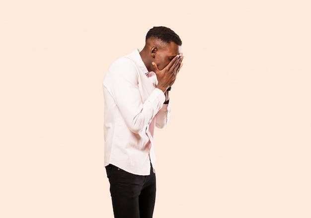 Jovem negro afro-americano com os olhos cônicos e as mãos com um olhar triste e frustrado de desespero, chorando, vista lateral na parede bege