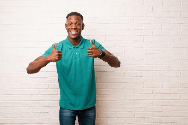 Jovem negro afro-americano com um sorriso largo, parecendo feliz, positivo, confiante e bem-sucedido, com os dois polegares apoiados na parede de tijolos