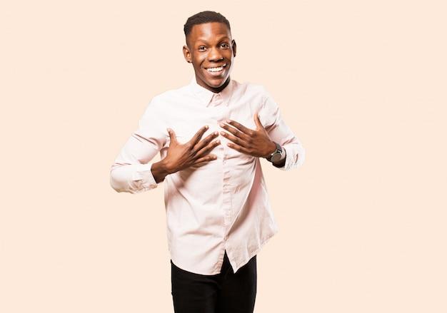 Jovem negro afro-americano parecendo feliz, surpreso, orgulhoso e animado, apontando para si mesmo na parede bege