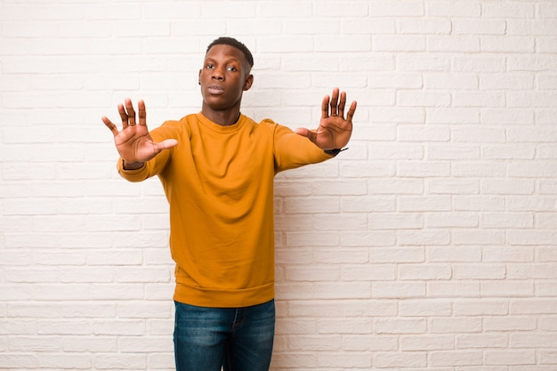 Jovem negro afro-americano parecendo sério, infeliz, zangado e descontente, proibindo a entrada ou dizendo pare com as duas mãos abertas na parede de tijolos