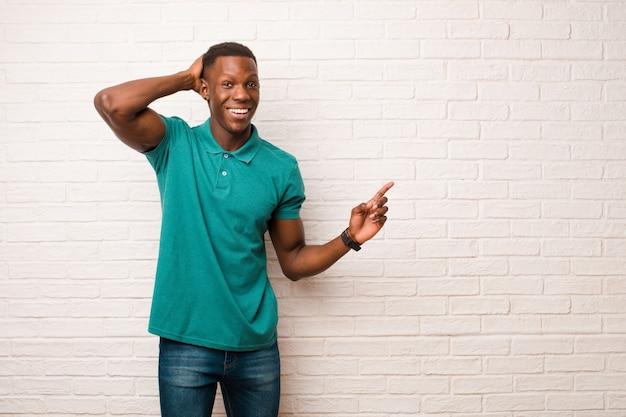 Jovem negro afro-americano rindo, parecendo feliz, positivo e surpreso, percebendo uma ótima ideia apontando para o espaço de cópia lateral na parede de tijolos