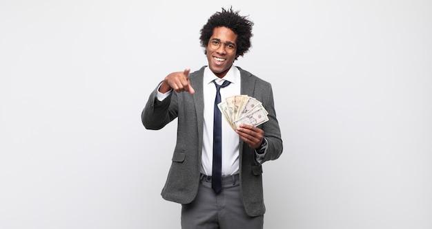 Jovem negro afro apontando para a câmera com um sorriso satisfeito, confiante e amigável, escolhendo você