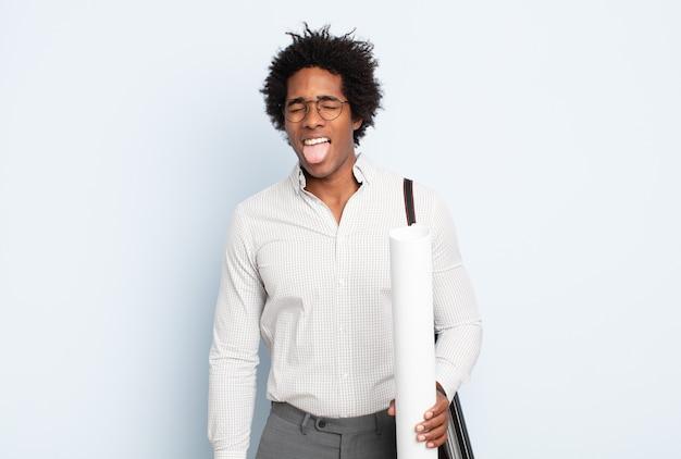 Jovem negro afro com atitude alegre, despreocupada, rebelde, brincando e mostrando a língua, se divertindo