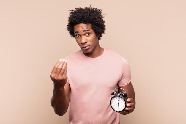 Jovem negro afro fazendo um gesto de capice ou dinheiro