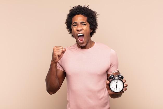 Jovem negro afro gritando agressivamente com uma expressão de raiva ou com os punhos cerrados celebrando o sucesso