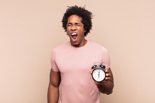 Jovem negro afro gritando agressivamente, parecendo muito zangado, frustrado, indignado ou irritado, gritando não