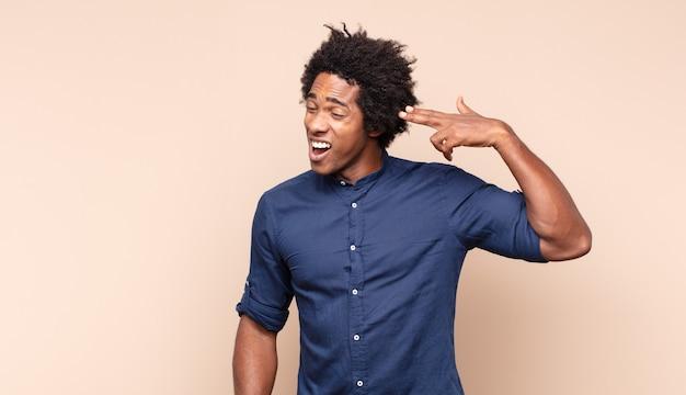 Jovem negro afro gritando alto e furiosamente para copiar o espaço ao lado, com a mão perto da boca