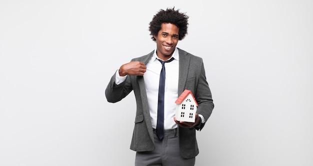 Jovem negro afro parecendo arrogante, bem-sucedido, positivo e orgulhoso, apontando para si mesmo