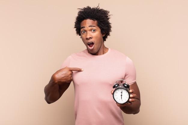 Jovem negro afro parecendo chocado e surpreso com a boca aberta, apontando para si mesmo