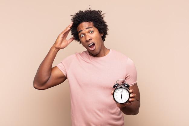 Jovem negro afro parecendo feliz, espantado e surpreso, sorrindo e dando uma boa notícia incrível