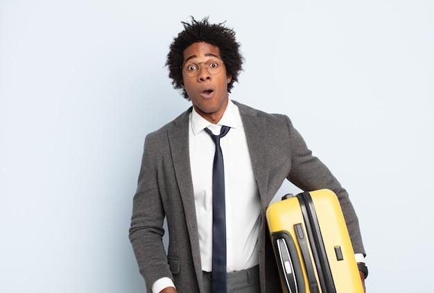 Jovem negro afro parecendo muito chocado ou surpreso, olhando com a boca aberta dizendo uau