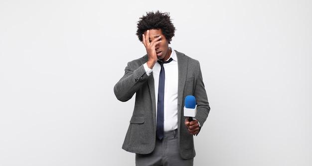 Jovem negro afro se sentindo entediado, frustrado e com sono depois de uma tarefa cansativa, enfadonha e tediosa, segurando o rosto com a mão