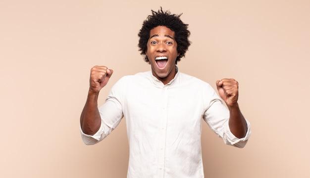 Jovem negro afro se sentindo feliz, positivo e bem-sucedido, comemorando a vitória, conquistas ou boa sorte