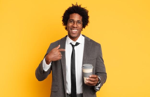 Jovem negro afro se sentindo feliz, surpreso e orgulhoso, apontando para si mesmo com um olhar empolgado e surpreso