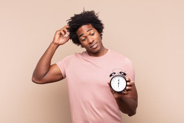 Jovem negro afro se sentindo perplexo e confuso, coçando a cabeça e olhando para o lado