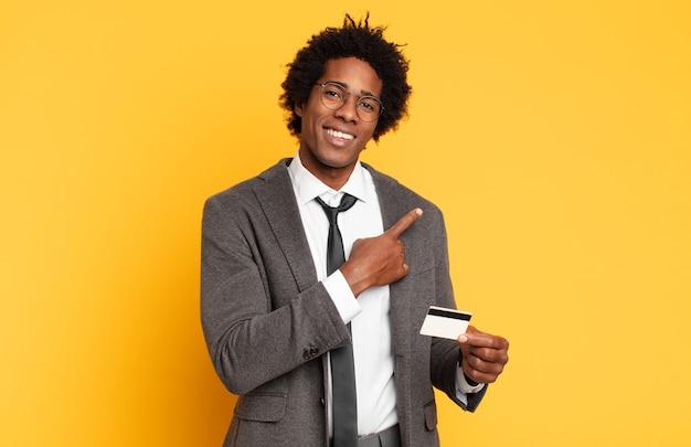Jovem negro afro sorrindo alegremente, se sentindo feliz e apontando para o lado e para cima, mostrando o objeto no espaço da cópia