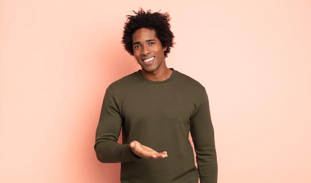 Jovem negro afro sorrindo alegremente, se sentindo feliz e mostrando um conceito no espaço da cópia com a palma da mão