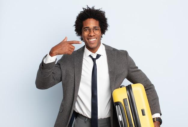 Jovem negro afro sorrindo com confiança apontando para o próprio sorriso largo