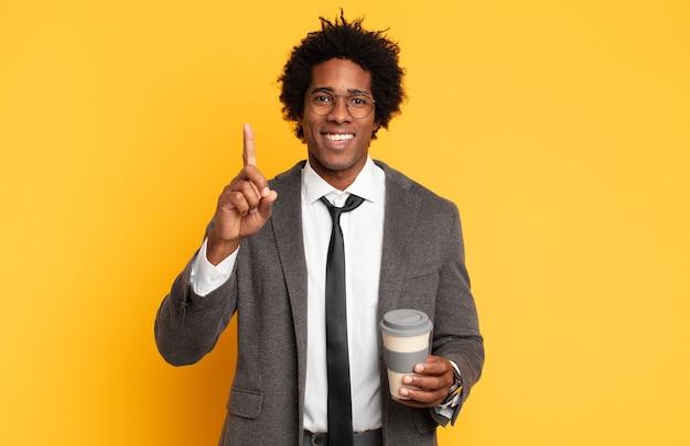 Jovem negro afro sorrindo com orgulho e confiança fazendo a pose número um triunfantemente, sentindo-se um líder