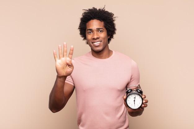 Jovem negro afro sorrindo e parecendo amigável, mostrando o número quatro ou o quarto com a mão para a frente, em contagem regressiva