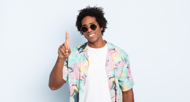Jovem negro afro sorrindo e parecendo amigável, mostrando o número um ou primeiro com a mão para a frente, em contagem regressiva