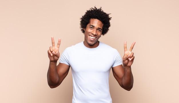 Jovem negro afro sorrindo e parecendo feliz, despreocupado e positivo, gesticulando vitória ou paz com uma das mãos